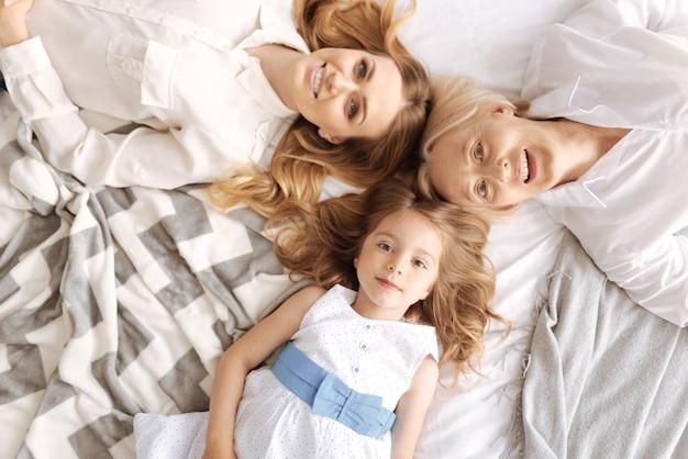Widok z góry trzech całkiem wesołych samic trzech pokoleń, w tym małej córeczki i jej matki z babcią, leżących na łóżku głowa przy głowie i uśmiechających się
