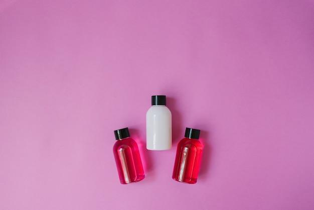Widok z góry trzech małych butelek białych i szkarłatnych oraz produktów do pielęgnacji ciała i włosów na różowym tle. kosmetyki dla turystów