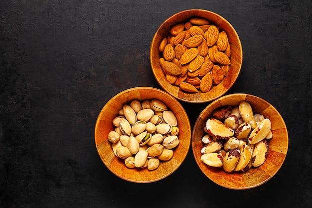 Widok z góry trzy drewniane miski z orzechami brazylijskimi, pistacjami i orzechami migdałowymi, stojące na starym rustykalnym.