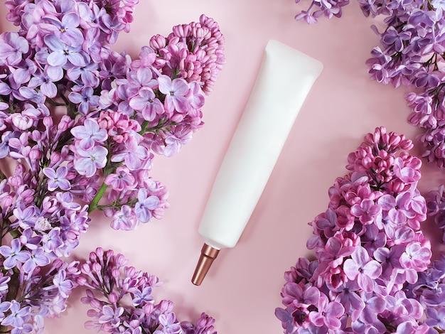 Widok z góry tubki kosmetycznej i różowych kwiatów bzu na różowym stole.
