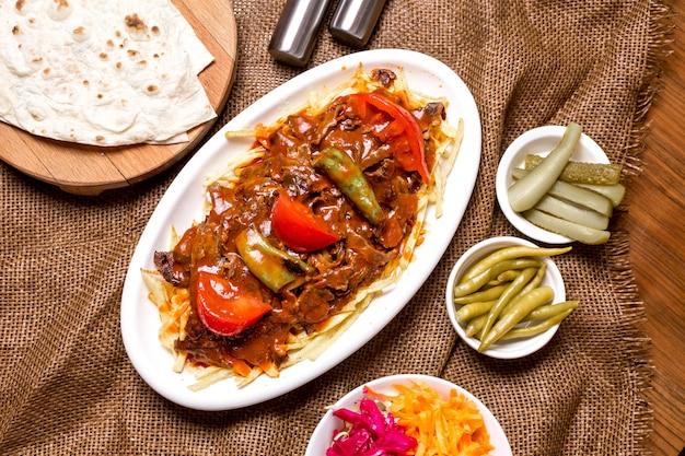Widok z góry tureckiego kebabu wołowego przyozdobionego pikantnym sosem pomidorowym podawanym z piklami