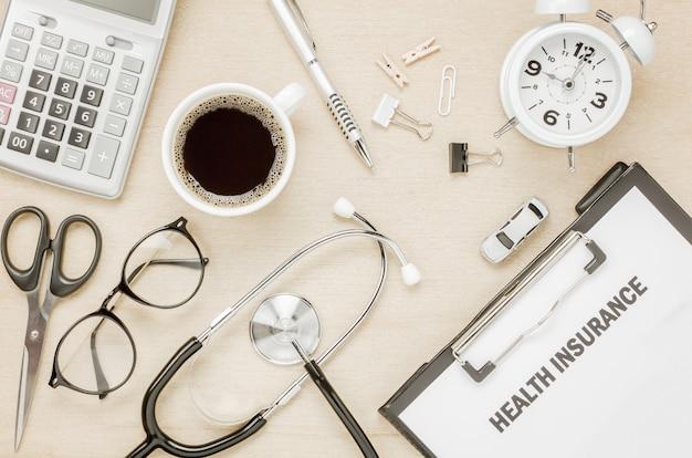Widok z góry ubezpieczenia zdrowotnego formularza i okulary zegara samochód nożyczki z stetoskop na tle drewniane.