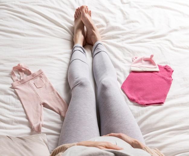 Widok z góry ubrania dla dzieci obok kobiety w ciąży