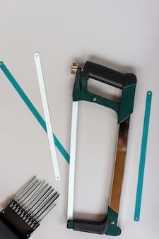Widok z góry uchwytu nowej piły do metalu na szarym tle. narzędzie pracy dla stolarzy.