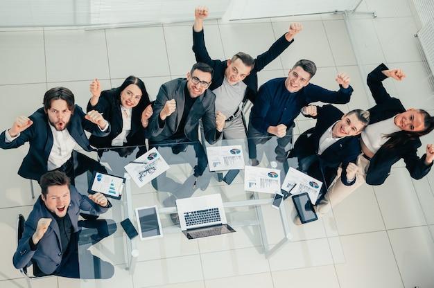 Widok z góry. udany zespół biznesowy siedzący przy biurku i patrzący w kamerę.
