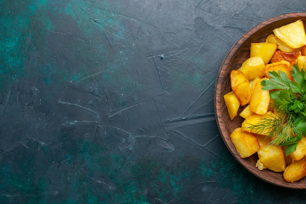 Widok z góry ugotowane pokrojone ziemniaki z zieleniną wewnątrz brązowego talerza na granatowym biurku