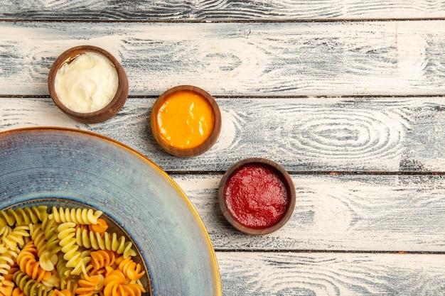 Widok z góry ugotowany makaron spiralny z różnymi przyprawami na szarym biurku z ciasta makaronowego w kolorze pieprzu
