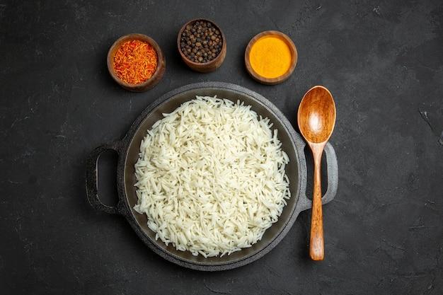Widok z góry ugotowany ryż wewnątrz patelni z przyprawami na ciemnej powierzchni posiłek jedzenie ryż wschodni obiad