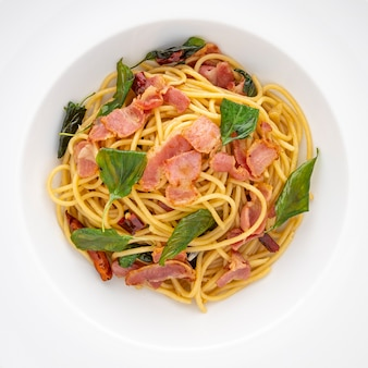 Widok z góry ujęcie makaronu spaghetti z suszonymi chili, czosnkiem, słodką bazylią i boczkiem w tle tekstury białego talerza ceramicznego, stosunek kwadratowy