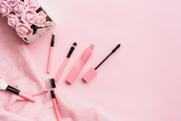 Widok z góry układ z elementami makijażu na różowym tle