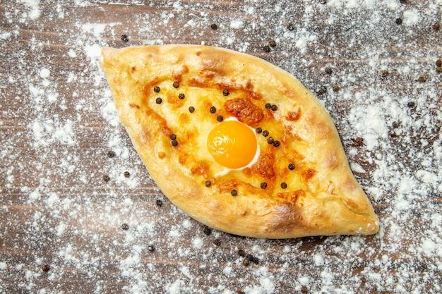 Widok z góry upieczony chleb z gotowanym jajkiem i mąką na brązowej powierzchni ciasta upiec jajka chleb bułka