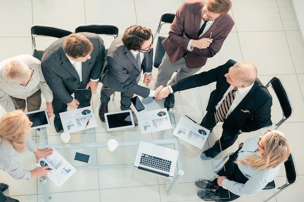 Widok z góry. uścisk dłoni partnerów finansowych na spotkaniu roboczym