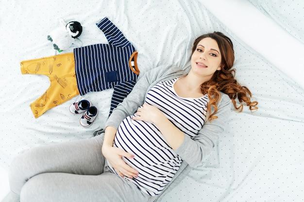Widok z góry uśmiechnięta kobieta w ciąży rasy kaukaskiej z długimi brązowymi włosami iw bluzce w paski ustanawiające