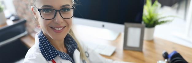 Widok z góry uśmiechnięta pielęgniarka patrząc na kamery ze szczęściem i spokojem. urządzenie do pomiaru ciśnienia. lekarz wypełniający formularz chorego. koncepcja opieki zdrowotnej i zapobiegania