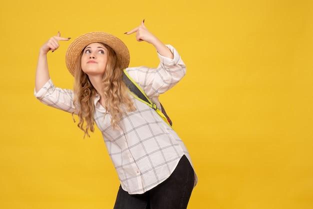 Widok z góry uśmiechnięta podróżująca dziewczyna w kapeluszu i plecaku, wskazując na żółto