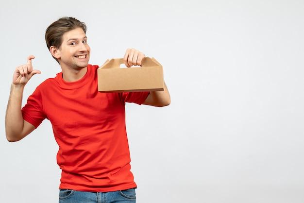 Widok z góry uśmiechniętego młodego człowieka w czerwonej bluzce, trzymając pudełko, robiąc coś dokładnego na białej ścianie