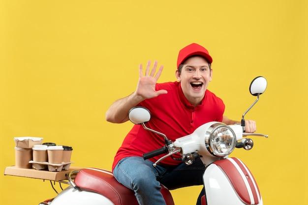 Widok z góry uśmiechniętego młodego dorosłego w czerwonej bluzce i kapeluszu, wykonującego zamówienia przedstawiające pięć na żółtej ścianie