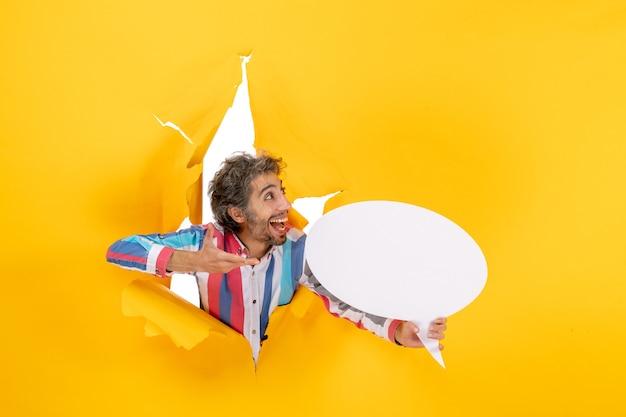 Widok z góry uśmiechniętego młodego mężczyzny wskazującego białą stronę z wolną przestrzenią w rozdartej dziurze w żółtym papierze