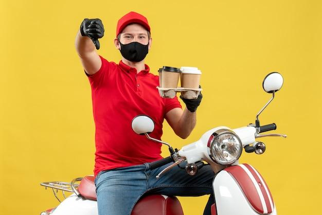 Widok z góry uśmiechnięty facet dostawy ubrany w rękawiczki mundurowe i kapeluszowe w masce medycznej, siedzący na skuterze, pokazujący porządek z kciukiem w dół