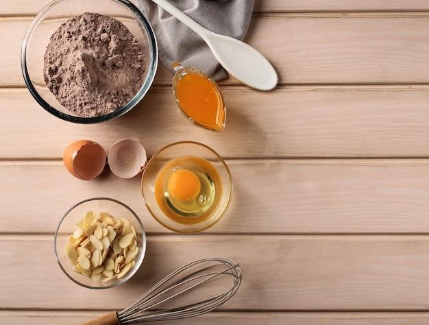 Widok z góry vintage drewniany stół kuchenny ze składnikami do pieczenia ciasta (jajka, mąka, masło, migdały, cukier), trzepaczką do pieczenia i łopatką wokół. kopiuj miejsce na tekst lub przepis