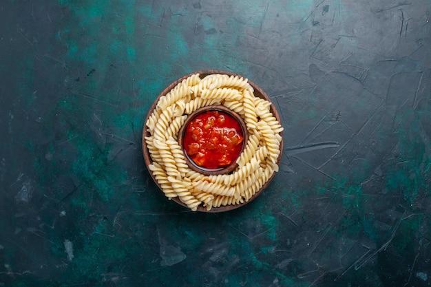 Widok z góry w kształcie włoskiego makaronu z sosem pomidorowym na granatowym biurku