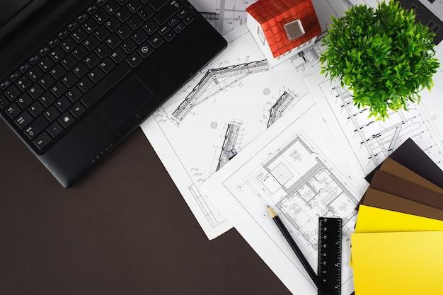 Widok z góry w miejscu pracy architekta. biały dom na rysunkach konstrukcyjnych, długopis do laptopa i próbki kolorów.