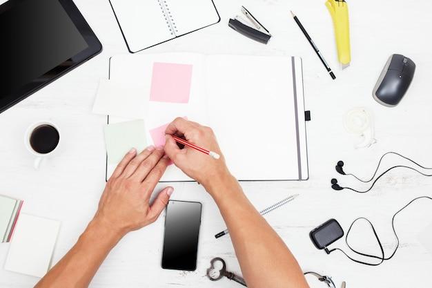 Widok z góry w miejscu pracy człowiek pracujący z nowoczesnymi urządzeniami i pisania na notebooku