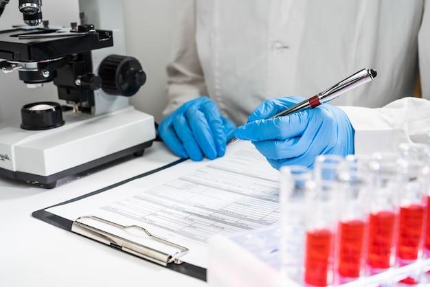 Widok z góry w miejscu pracy lekarza. probówki z badaniami krwi, lekarz zapisuje wyniki w formie