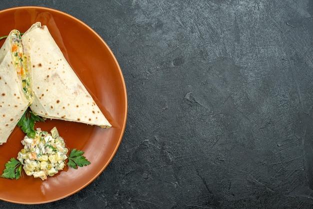 Widok z góry w plasterkach shaurma smaczna kanapka z mięsem wewnątrz talerza na ciemnym biurku burger kanapka chleb pita mięso