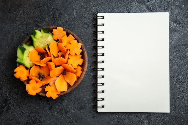 Widok z góry w plasterkach zaprojektowana sałatka z notatnikiem na szarym tle sałatka zdrowotna dieta warzywna