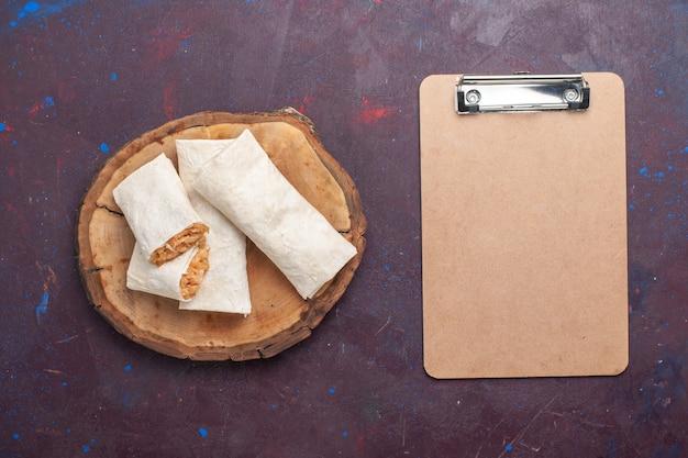 Widok z góry walcowane ciasto z nadzieniem mięsnym i notatnikiem na ciemnym tle