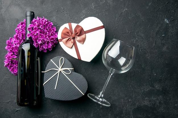 Widok z góry walentynki prezent z butelką wina i kwiatami na ciemnym tle miłość uczucie para prezent kolor alkohol małżeństwo