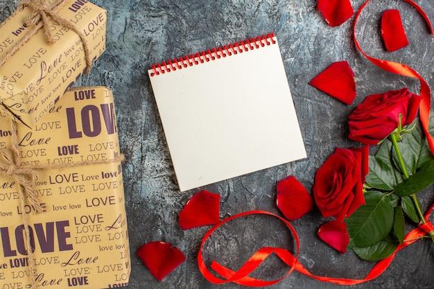 Widok z góry walentynki prezent z czerwonymi różami i płatkami na szarym tle para małżeństwo miłość wakacje uczucie serce pasja