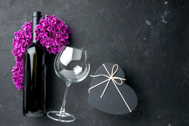 Widok z góry walentynki prezent z kwiatami i butelką wina na ciemnym tle miłość uczucie para prezent kolor alkohol małżeństwo