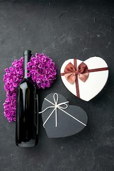 Widok z góry walentynki prezent z kwiatami i butelką wina na ciemnym tle miłość uczucie para prezent kolory alkohol małżeństwo