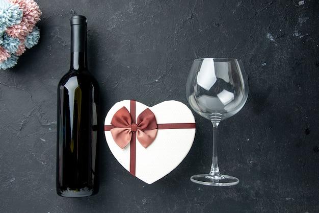 Widok z góry walentynki prezent z kwiatami i winem na ciemnym tle miłość uczucie para prezent kolor alkohol