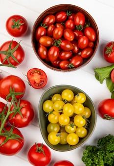 Widok z góry warzyw jak kolendra szpinak pomidorowy z miskami pomidorów na drewnie
