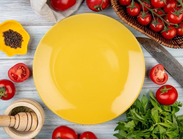 Widok z góry warzyw jako liście mięty zielonej pomidora z kruszarką czosnku i pieprzu czarnego pieprzu oraz nożem z pustym talerzem na drewnianej powierzchni