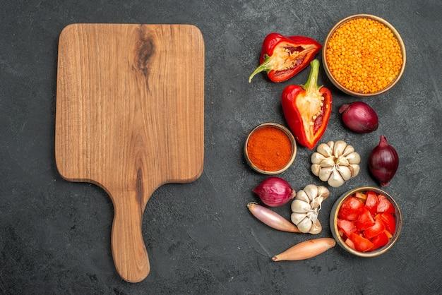 Widok z góry warzywa drewniana deska do krojenia papryka dzwonek cebula pomidory przyprawy czosnek