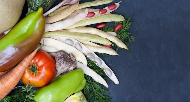 Widok z góry warzywa i fasoli na ciemnym tle. zdrowe jedzenie wegetariańskie. . leżał płasko