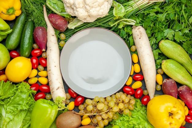 Widok z góry warzywa i owoce pomidory koktajlowe cumcuat sałata pigwa winogrona cytryna kalafior biała rzodkiew pietruszka talerz cukinia na środku