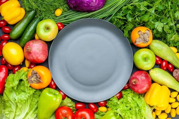 Widok z góry warzywa i owoce sałata pomidory rzodkiew ogórek koperek pomidory koktajlowe granat persymona jabłko szary talerz na środku