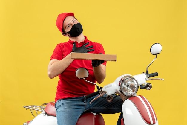 Widok z góry wdzięcznego kuriera w czerwonej bluzce i rękawiczkach w masce medycznej siedzi na skuterze, pokazując porządek
