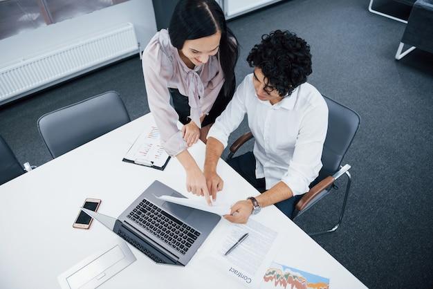 Widok z góry. wesoły współpracowników w nowoczesnym biurze, uśmiechając się, gdy wykonują swoją pracę za pomocą laptopa