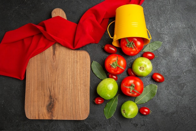 Widok z góry wiadro z czerwonymi zielonymi i pomidorkami cherry, liście laurowe, czerwony ręcznik i deska do krojenia na ciemnym tle