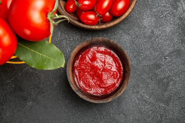 Widok z góry wiadro z pomidorami i miseczkami z liści laurowych z pomidorami cherry i keczupem na ciemnym podłożu