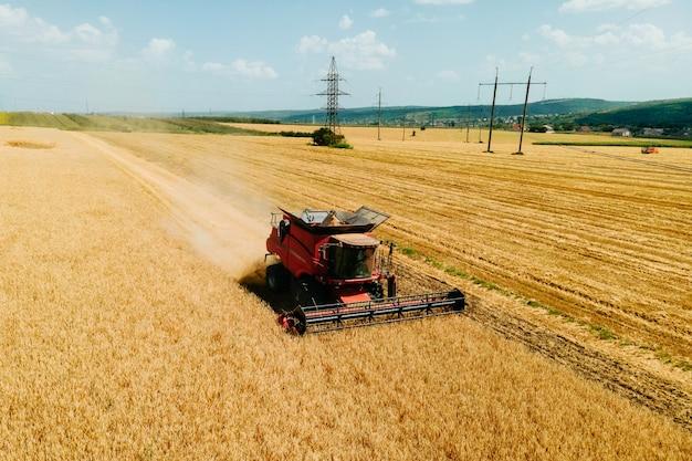 Widok z góry widok z lotu ptaka kombajnu zbożowego zbierającego plony pszenicy w okresie letnim kombajn...