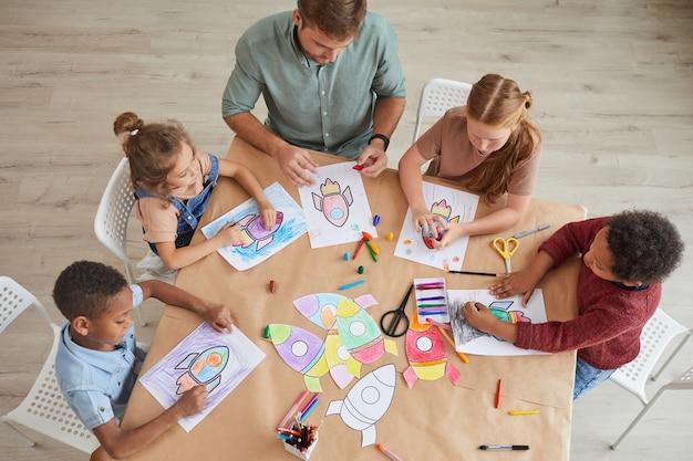 Widok z góry wieloetnicznej grupy dzieci rysujących obrazki rakiet kosmicznych kredkami podczas zajęć plastycznych i rzemieślniczych w przedszkolu lub centrum rozwoju