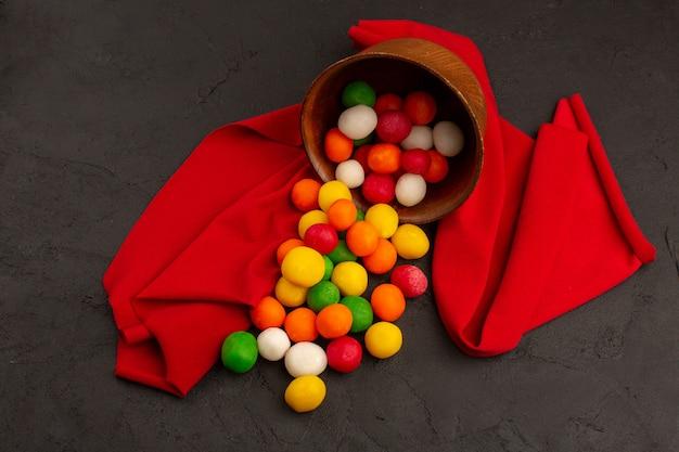 Widok z góry wielokolorowe cukierki słodkie wewnątrz brązowego garnka na czerwonej tkance i ciemne