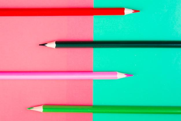 Widok z góry wielokolorowe kredki na różowym i jasnozielonym tle